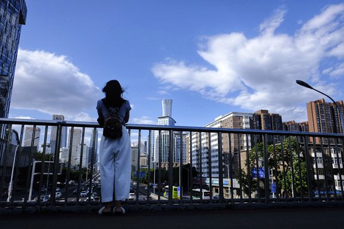 A woman in Beijing enjoys clear skies on Friday with the density of PM2.5 in the city only 0.1 micrograms per cubic meter. Netizens dubbed it as