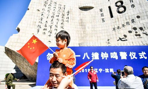 Visitors holding Chinese national flags have their photos taken in front of the 9.18 Historical Museum in Shenyang, Northeast China's Liaoning Province on Wednesday. Air raid sirens once again sounded through the city at 9:18 am on Wednesday. The