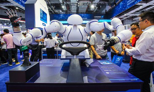 Visitors look at a service robot at the 21st China International Industry Fair in Shanghai on Tuesday. Photo: VCG