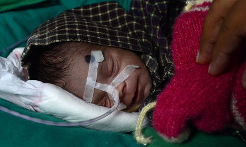 A newborn baby girl rests at a hospital in Bareilly in northern India's Uttar Pradesh state on Wednesday, where she is recovering after being found buried alive in an earthen pot. A man digging a grave in northern India found the girl, police said Monday, in the latest case to shine a spotlight on female infanticide in the country. Photo: AFP