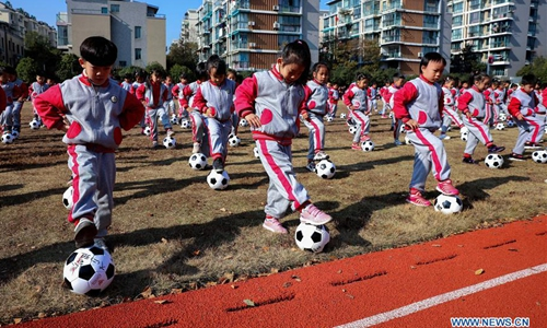 Students perform with footballs during a football themed activity at a kindergarten in Changxing County of east China's Zhejiang Province, Dec. 9, 2019. (Xinhua/Xu Yu)