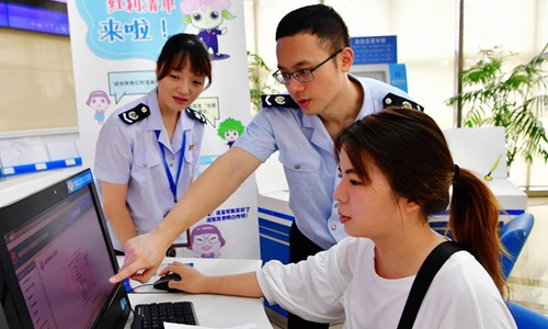 Staff members of tax service help a financial staff of a company (R) to print out a list of her company's tax cuts and fee reductions in Fuzhou, capital of southeast China's Fujian Province, Aug. 21, 2019. An online service of clearly listing the cut of taxes and fees has been promoted in the whole province of Fujian after sucessfully piloted in the city of Fuzhou.Photo:Xinhua