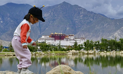 A child plays by a lake at Nanshan Park in Lhasa, southwest China's Tibet Autonomous Region, July 30, 2019.(Xinhua/Zhang Rufeng)