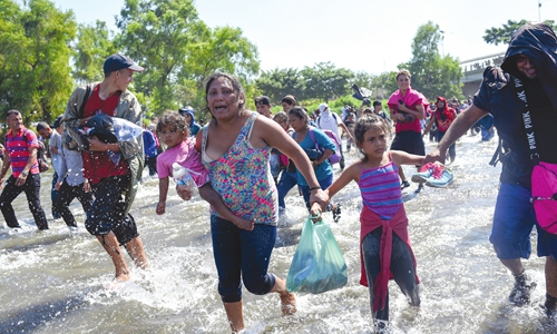 Central American migrants - mostly Hondurans traveling in caravan to the US - cross the Suchiate River, the natural border between Guatemala and Ciudad Hidalgo, Mexico on Monday. Photo: AFP
