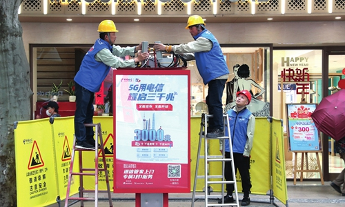 Workers from China Telecom install mini 5G base stations at a telephone booth in Shanghai on Friday. The company is expected to install similar 5G equipment in more than 100 telephone booths by the end of the year. China is investing billions of yuan in the field. Photo: AFP