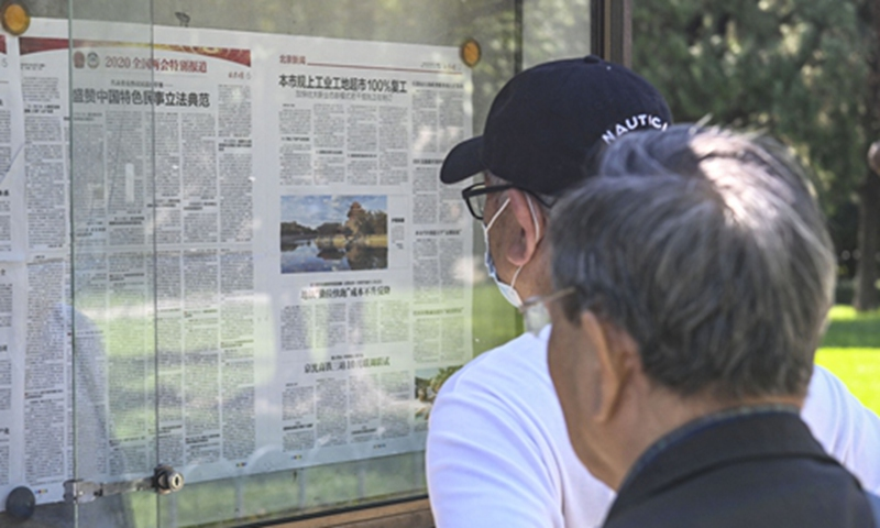 Local residents read reports about a draft civil code being deliberated at the two sessions in front of an outdoor newspaper display board in a park in Beijing on Tuesday. Photo: cnsphoto