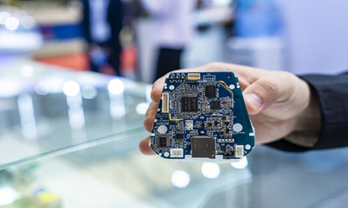 An employee showcases a semiconductor integrated circuit at an industry expo on October 31. Photo: VCG