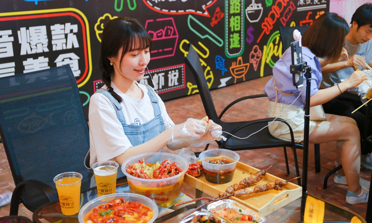 A female anchor of celebrity beauty in short video platform Douyin shares the delicious food with netizens while eating crayfish on June 6. The booming night market of Shanghai nightlife festival promoted the economy of eating show. Photo: IC