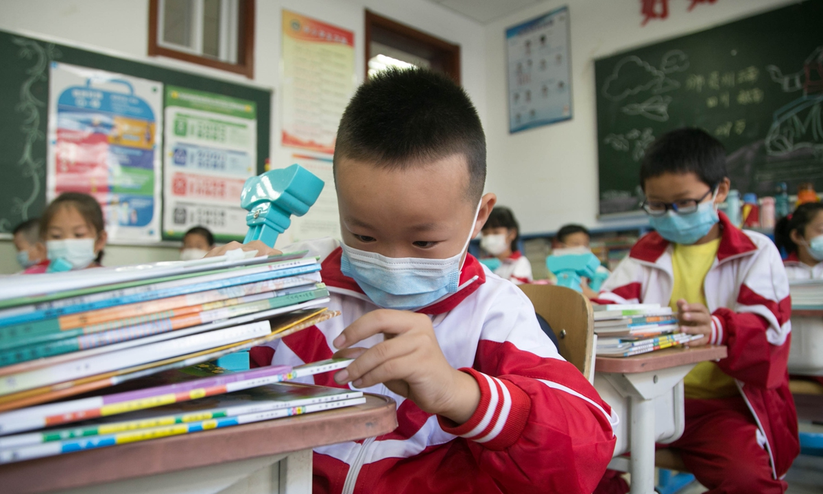 Grade four students in Beijing sort books at a school on Monday. All students in elementary and middle schools in Beijing return to school on Monday after the epidemic ebbs. Photo: VCG