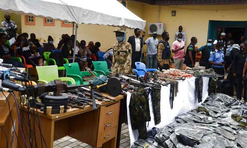 Weapons, ammunition and counterfeit military uniforms are displayed in an event showcasing Nigerian police's achievements in fighting illegal militants in Abuja, Nigeria on Sept. 30, 2020. Nigerian police have recently stepped up fight against robbers, kidnappers and illegal armed groups in different parts of the country. (Photo by David Oma/Xinhua)
