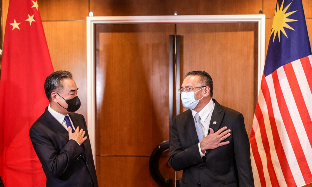 Chinese State Councilor and Foreign Minister Wang Yi (left) and Malaysian Foreign Minister Hishammuddin Hussein share a light moment before their meeting in Kuala Lumpur on Tuesday. China and Malaysia have reached consensus on a wide range of issues, including strengthening bilateral cooperation, fighting COVID-19, upholding multilateralism, and maintaining peace and stability in the South China Sea. Photo: AFP