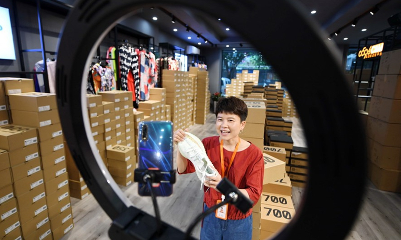A staff sells shoes through live streaming at an e-commerce warehouse in Putian, southeast China's Fujian Province, May 7, 2020.Photo:Xinhua