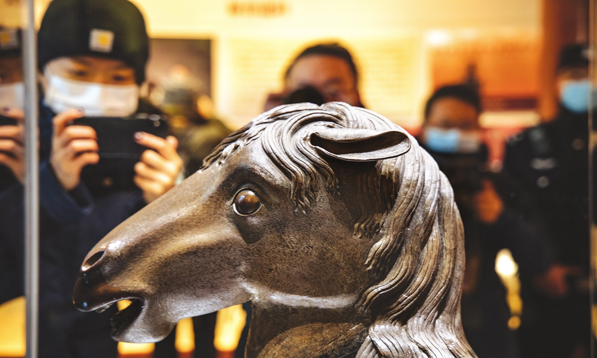 Visitors take pictures of the bronze horse zodiac head that was stolen by invading forces when British and French troops razed the Old Summer Palace in 1860. The statue finally returned to its home, Yuanmingyuan, or the Old Summer Palace, on Tuesday. Photo: Li Hao/GT