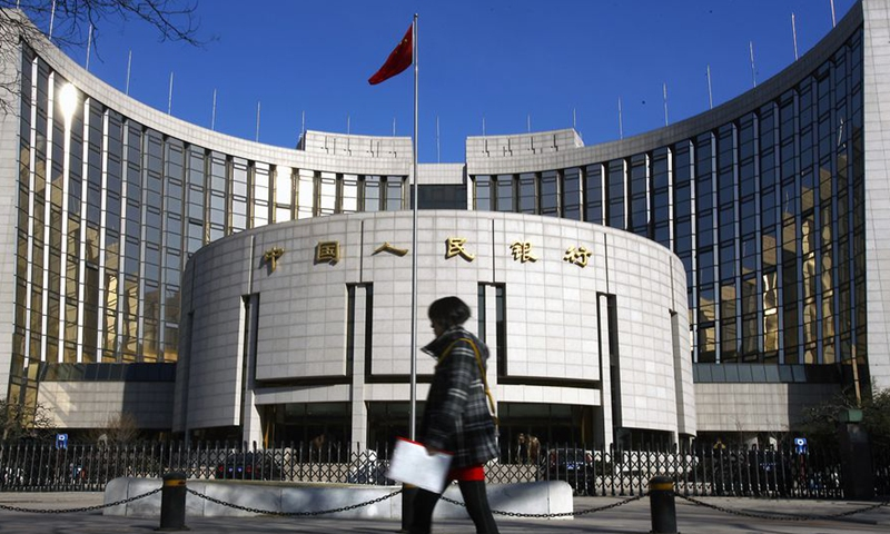 A file photo shows a pedestrian walks past the headquarters building of the People's Bank of China in Beijing, capital of China. (Xinhua)