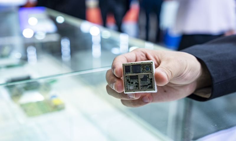 An employee showcases a semiconductor integrated circuit at an industry expo. Photo: VCG