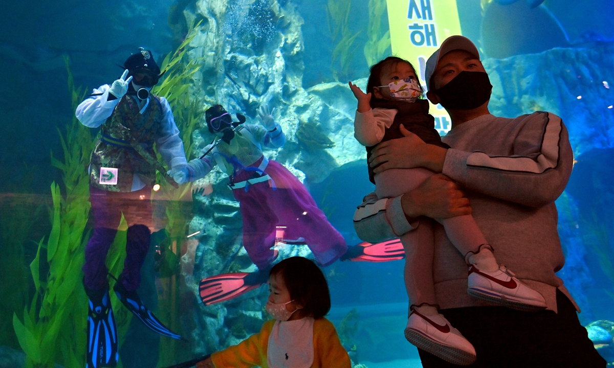 South Korean divers wearing traditional Korean hanbok dress pose in an aquarium for visitors during an event to celebrate the New Year at Lotte World Aquarium in Seoul on Sunday. Photo: AFP