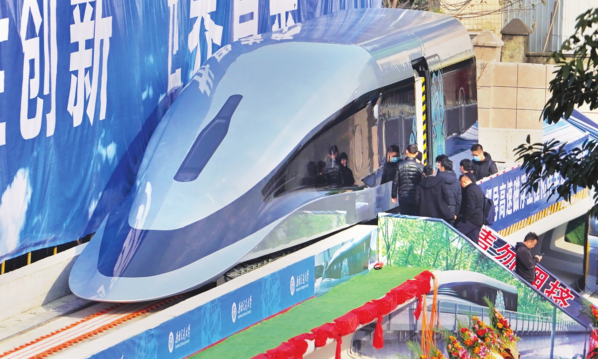 People visit a prototype of a domestically developed superconducting maglev train that rolled off the production line on Wednesday in Chengdu, Southwest China's Sichuan Province. The train, dubbed the