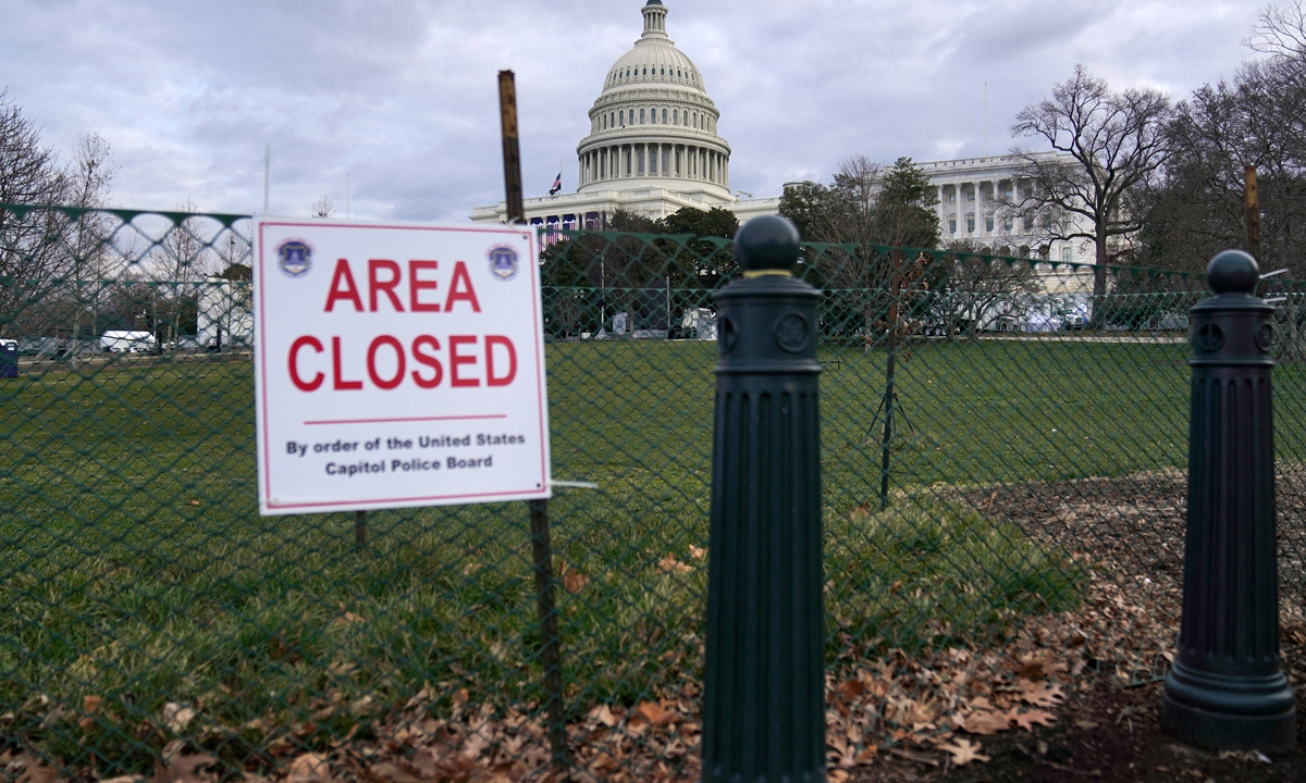A sign reading Area Closed is posted on fencing outside the US Capitol on Sunday in Washington, DC. After riots at the Capitol Building, the FBI has warned of additional threats in the nation's capital and in all 50 states. According to reports, as many as 25,000 National Guard soldiers will guard the city as preparations are made for the inauguration of Joe Biden as the 46th US President. Photo: AFP