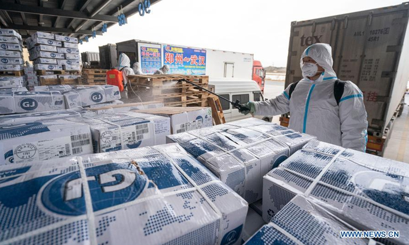 A staff member sprays disinfectant on the package of imported cold chain food at a regional cold chain center in Wuhan, capital of central China's Hubei Province, Jan. 7, 2021. (Xinhua/Xiong Qi)