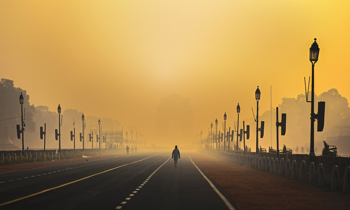 A man walks along Rajpath in smog in New Delhi on Thursday. The capital city of India continued to experience dense fog on Thursday with air quality in the