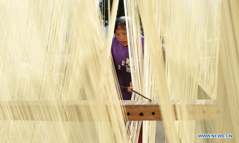 He Yunxiao airs handmade noodles at Longmen Village, Majian Township, Zhuji City of east China's Zhejiang Province, Jan. 29, 2021. There are more than a dozen steps in the traditional process of handmade noodles in Majian. These noodles, well noted for their length, symbolize longevity in the Chinese culture. Longmen Village alone turns out about 1,000 kilograms of handmade noodles a day, and brings in an annual income of some 2 million yuan (310,000 U.S. dollars). (Xinhua/Han Chuanhao)
