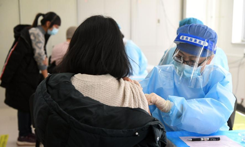 A medical worker (R) inoculates a recipient with a 2nd dose of COVID-19 vaccine at a temporary vaccination site in Haidian District of Beijing, capital of China, Jan. 29, 2021. The administration of the second dose of COVID-19 vaccines for key groups of residents throughout Beijing started on Jan. 22, and is expected to conclude before Feb. 8.Photo:Xinhua