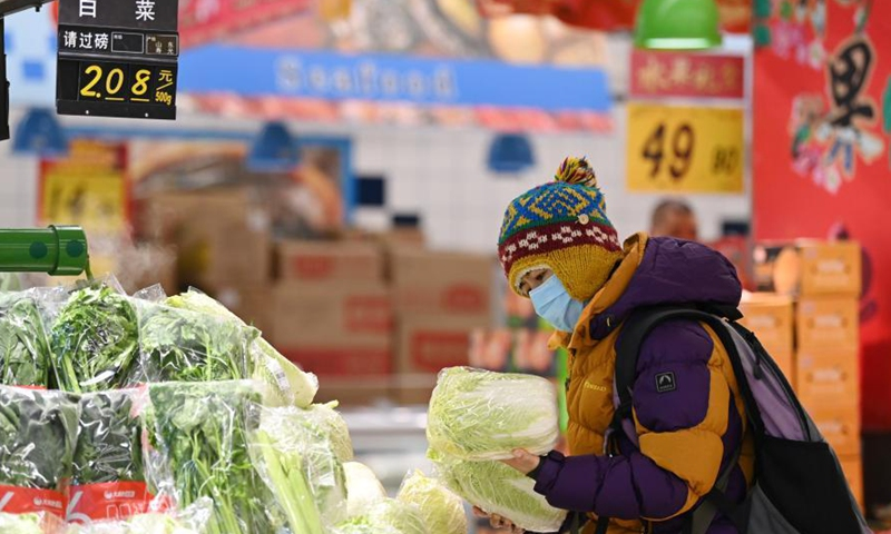 A resident selects vegetables at a supermarket in Xiangfang District of Harbin, northeast China's Heilongjiang Province, Jan. 30, 2021. Price and supply of daily necessities are stable in Harbin amid the ongoing COVID-19 pandemic, local authorities told a press briefing here on Saturday. (Xinhua/Wang Jianwei)