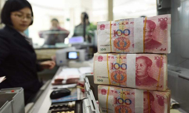 A bank staff member checks RMB banknotes at a bank in Lianyungang, east China's Jiangsu Province, Jan. 7, 2016.Photo:Xinhua