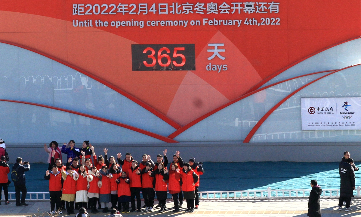 Sports fans, volunteers and the public gather in front of the one-year countdown board of the Beijing 2022 Winter Olympic Games and shout
