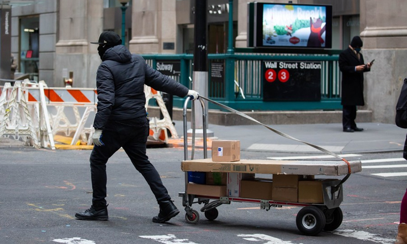 A delivery worker rolls packages across Wall Street in New York, United States, Jan. 8, 2021. (Photo by Michael Nagle/Xinhua)