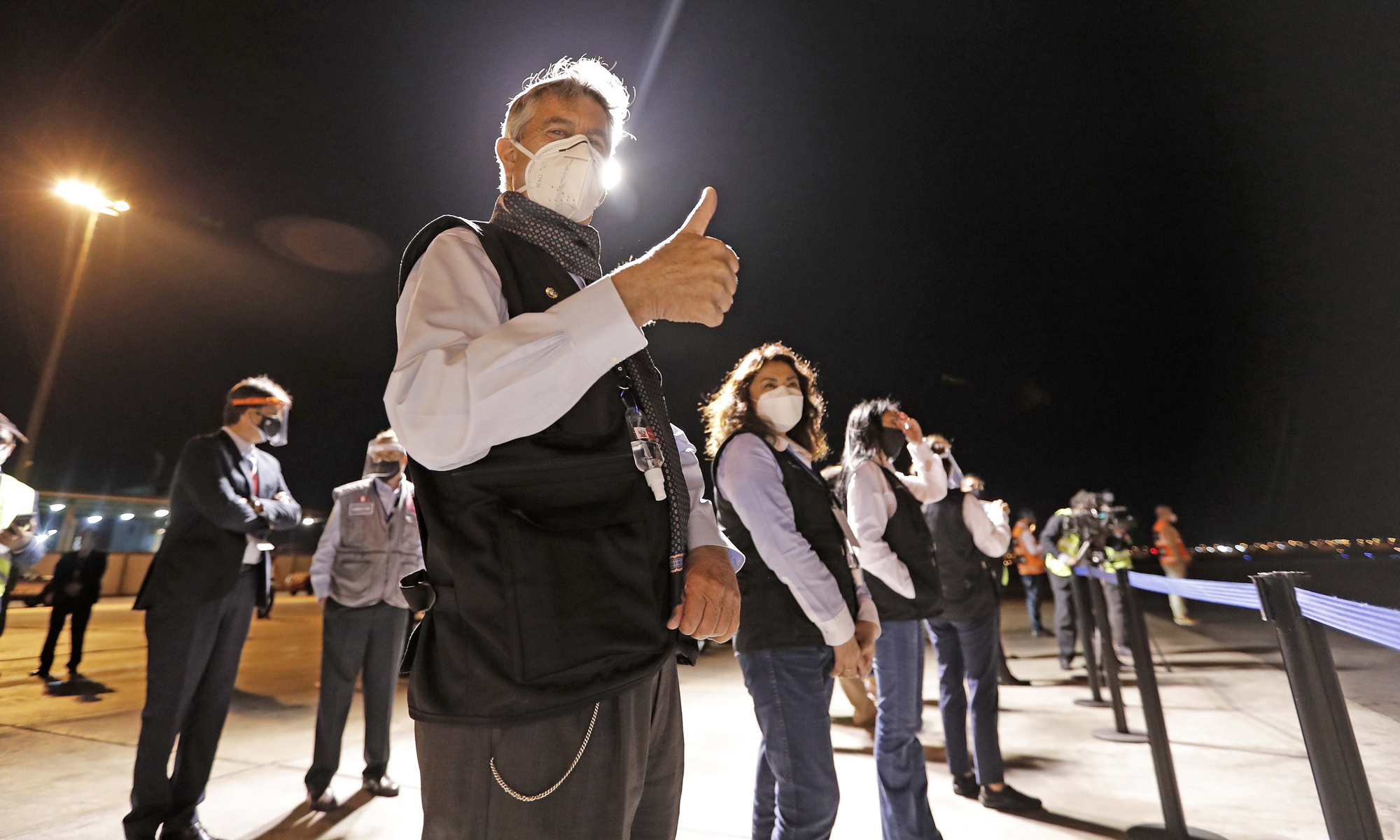 A handout photo provided by the Peruvian presidency shows President Francisco Sagasti (front) reacting during the arrival of the Air France plane with the first batch of COVID-19 vaccine at the Jorge Chavez airport in Lima, Peru on Sunday.  Peru received its first 300,000 vaccines amid a critical oxygen shortage due to a spike in COVID-19 cases. Photo: IC