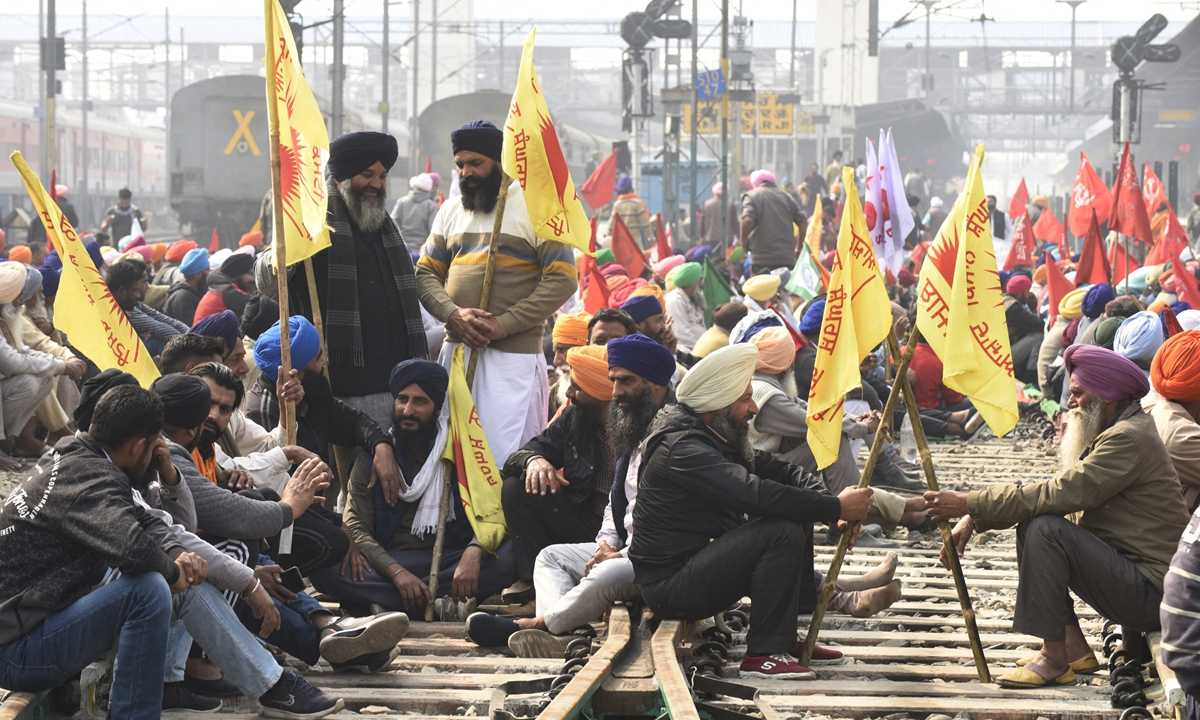 Farmers block railway tracks during a four-hour rail blockade as they continue their protest against the central government's recent agricultural reforms, at a railway station in Amritsar, India on Thursday. Authorities deployed thousands of security forces at railroad stations and tracks to prevent violence. Photo: AFP