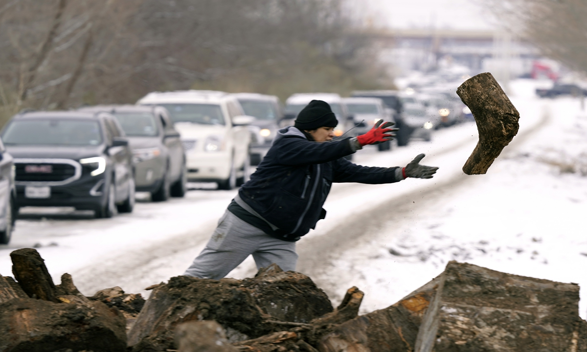 A resident tosses firewood as people line up to load up Wednesday in Dallas. Millions of people in the US have been hit by rolling blackouts or the complete shutoff of electricity in Texas caused by a winter storm. Photo: AP