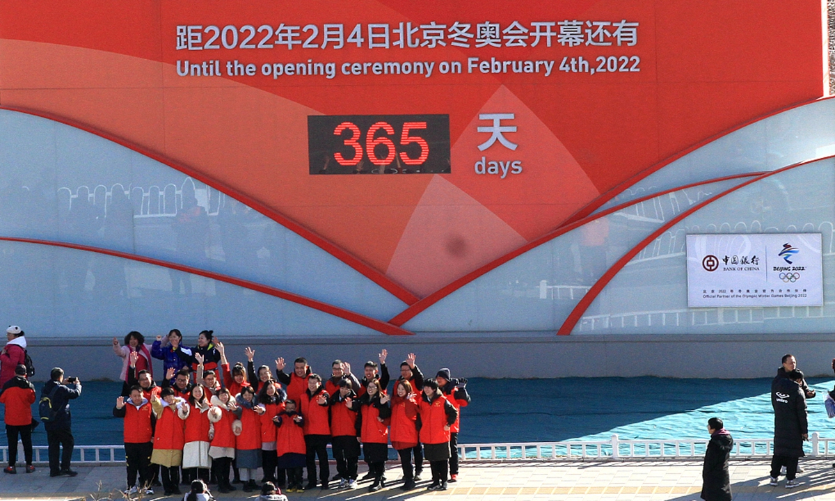 Sports fans, volunteers and the public gather in front of the one-year countdown board of the Beijing 2022 Winter Olympic Games and shout 2022, here we come in co-host city Zhangjiakou, North China's Hebei Province. The Winter Games organizer unveiled the designs of the Olympic torches on Thursday, just one year to go before the Games start. Photo: VCG