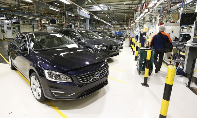 File photo taken on May 24, 2017 shows a worker walks past newly-assembled cars at the Volvo Car Gent in Ghent, Belgium. Volvo Car Gent, the second largest Volvo assembly line except that in Sweden, was purchased by the Chinese car manufacturer Geely Holding Group in 2010.Photo:Xinhua
