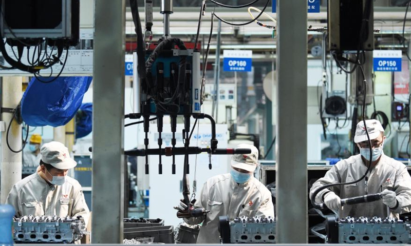 People work at a workshop of Harbin Dongan Automotive Engine Manufacturing Co., Ltd. in northeast China's Heilongjiang Province, Feb. 25, 2021. In January 2021, the company's product sales and sales revenue increased by 10.79 percent and 18.34 percent year on year respectively. (Xinhua/Wang Jianwei)
