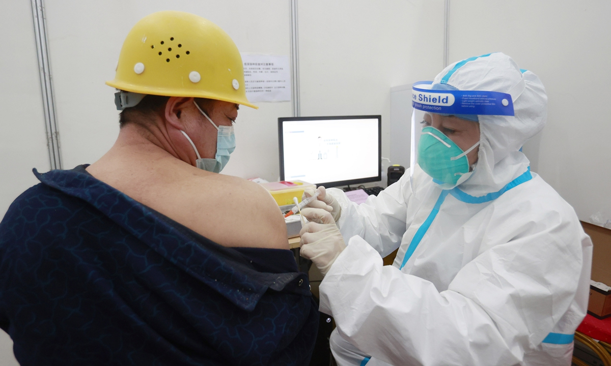 A construction worker for the Beijing Winter Olympic Games venues receives a COVID-19 vaccine on Tuesday in the capital city. Beijing has vaccinated more than 5 million residents and 2.64 million have received two doses. Photo: cnsphoto