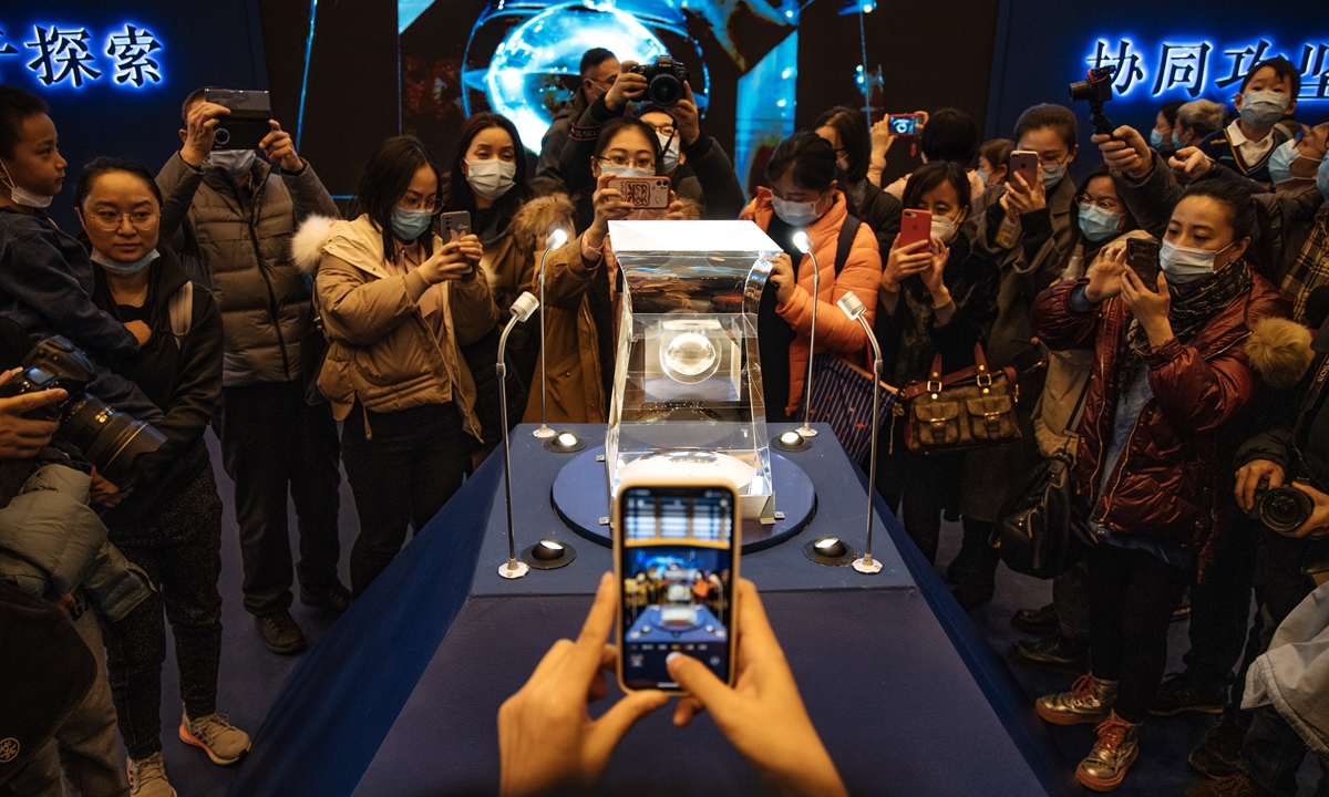 Visitors take photos of soil samples from moon retrieved by the Chang'e-5 lunar lander in December 2020, which went  on display at the National Museum of China in Beijing on Sunday. Scientific and technological objects related to the lunar exploration project are also on display at the exhibition. Photo: Li Hao/GT