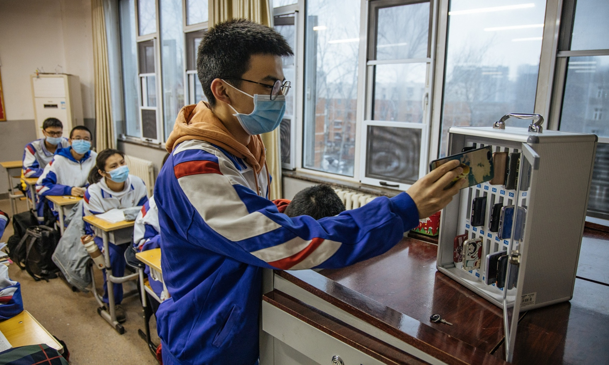 A student in Beijing Jinyuan School puts his mobile phone into the safe deposit box installed in the classroom on March 1, the first day of the new semester.Photo: Li Hao/GT