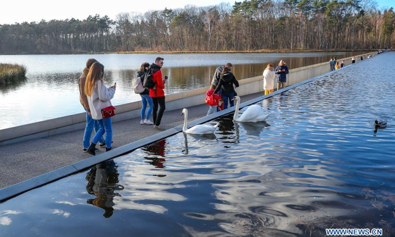People walk at the 'Cycling through Water' path in Bokrijk, Belgium, Feb. 27, 2021. 'Cycling through Water' is a path offering a unique experience in which people can cycle or walk more than 200 meters through a pond. The path opened in April 2016 and attracted many cyclists and hikers.(Photo: Xinhua)