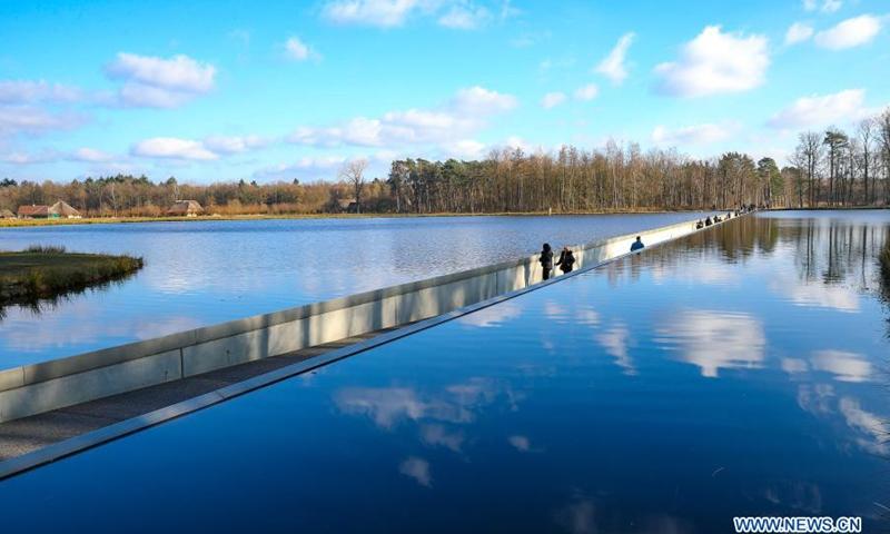 La photo aérienne prise le 27 février 2021 montre des personnes marchant le long de la route `` Cyclisme sur l'eau '' à Bokrijk, en Belgique.  «Faire du vélo dans l'eau» est un itinéraire qui offre une expérience unique où les gens peuvent faire du vélo ou marcher plus de 200 mètres à travers un étang.  L'itinéraire a ouvert en avril 2016 et a attiré de nombreux cyclistes et randonneurs.  (Photo: Xinhua)