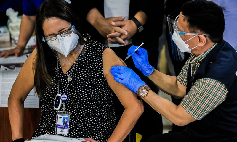 Philippine Department of Health Secretary Francisco Duque III injects a shot of COVID-19 vaccine from China's Sinovac to a doctor on the first day of the vaccination at the Lung Center of the Philippines in Manila, the Philippines on March 1, 2021. (Photo: Xinhua)