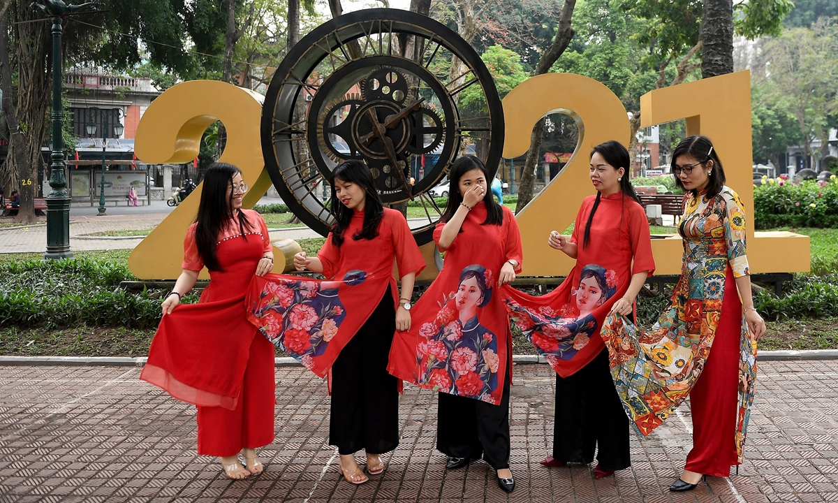 Woman wearing the traditional Vietnamese Ao Dai dress pose for a photograph along a street in Hanoi, Vietnam on Wednesday. Photo: AFP