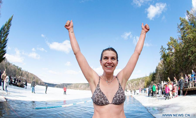 A swimmer reacts as she takes part in a winter swimming race on the Green Lake in Vilnius, Lithuania, on March 6, 2021. A 25-meter winter swimming race was held here on Saturday.Photo:Xinhua