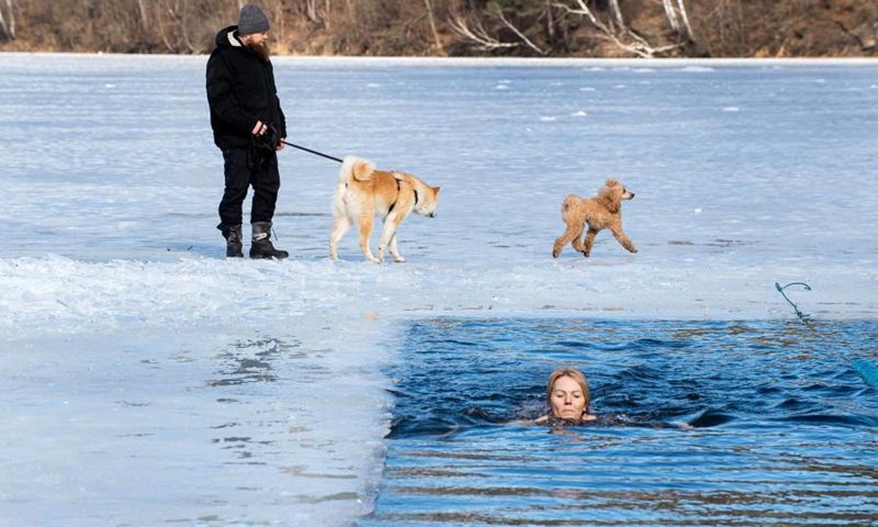 A swimmer takes part in a winter swimming race on the Green Lake in Vilnius, Lithuania, on March 6, 2021. A 25-meter winter swimming race was held here on Saturday.Photo:Xinhua