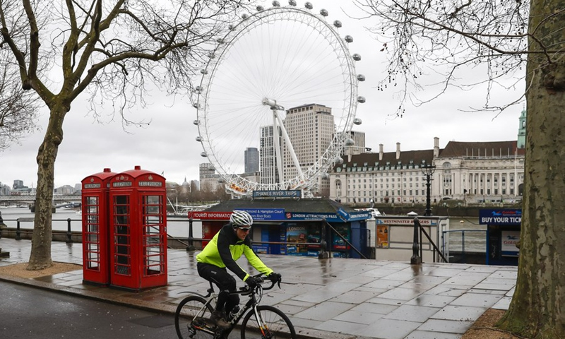 A man cycles past the London Eye by the Thames in London, Britain, on Feb. 17, 2021.(Photo: Xinhua)