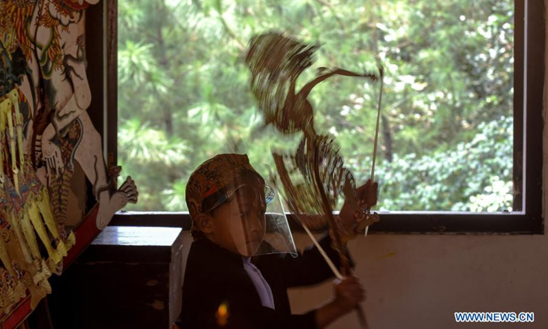A beginner student practices playing Javanese puppets following health protocols amid the COVID-19 pandemic at Nirmala Sari hermitage in Cinere, Depok district, West Java, Indonesia, March 7, 2021.(Photo: Xinhua)