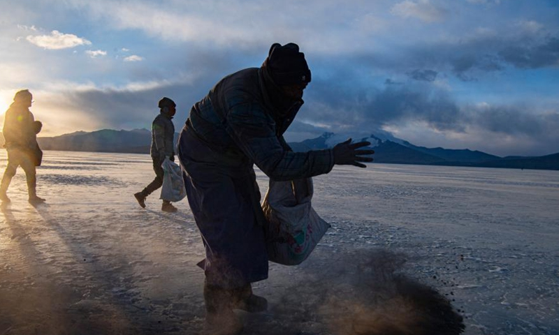Villagers spread cow dung and stove ashes to make a safe path on the frozen Puma Yumco Lake, southwest China's Tibet Autonomous Region, March 6, 2021.Photo:Xinhua