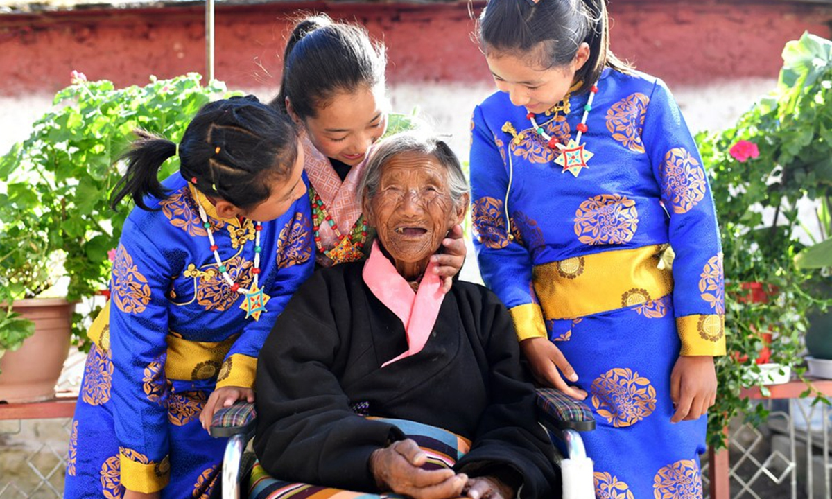 Sonam Drolma, 109, talks with her great granddaughters in the courtyard at home in Reguo Village of Gyaca County in Shannan, southwest China's Tibet Autonomous Region, March 24, 2020. (Xinhua/Zhan Yan)