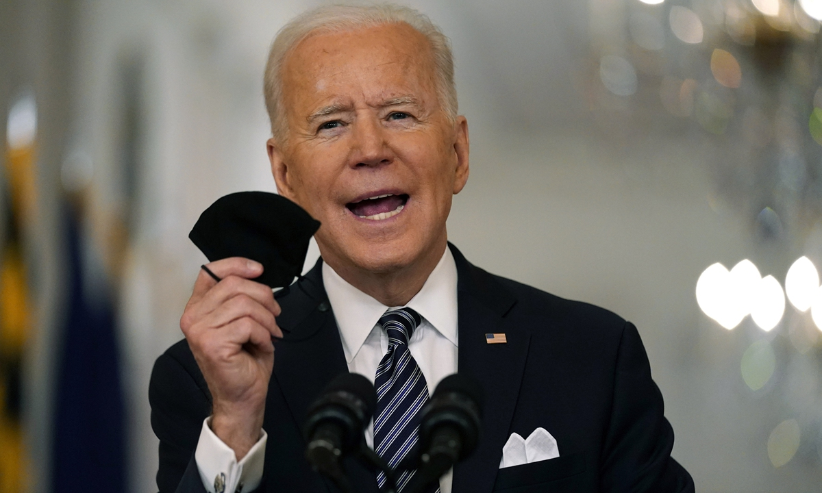 US President Joe Biden holds up his face mask as he speaks about the COVID-19 pandemic during a primetime address from the East Room of the White House on Wednesday in Washington. Photo: AP